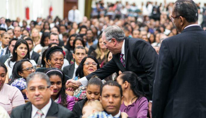 El élder Neil L. Andersen saluda a los miembros en Salvador. A la derecha está el presidente de la estaca Salvador Brasil, Lourival Feitosa Pita. Crédito: Reserva Intelectual, Inc.