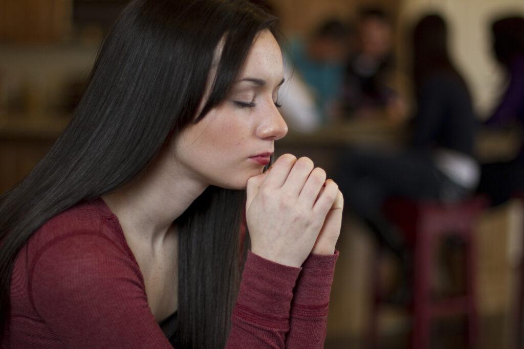 Una mujer joven reza. Crédito: Intellectual Reserve, Inc.